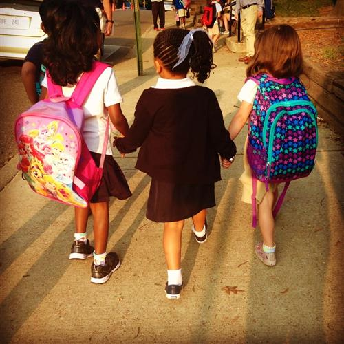 three students walk togetherer